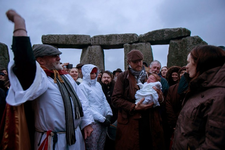 Rollo Maughfling, Archdruid of Stonehenge & Britain, (L) blesses baby Jim, held by his father Dan Lobb and watched by mum Kirsty Lobb as druids, pagans and revellers gather, hoping to see the sun rise as they take part in a winter solstice ceremony at Stonehenge on December 21, 2013 in Wiltshire, England. Despite the rain and wind, a large crowd gathered at the famous historic stone circle to celebrate the sunrise closest to the Winter Solstice, the shortest day of the year - an event claimed to be more important in the pagan calendar than the summer solstice, because it marks the 're-birth' of the Sun for the New Year.