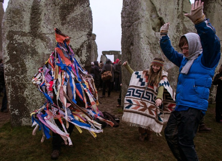 People dance as a man dressed in a rag costume plays an accordion, as druids, pagans and revellers gather, hoping to see the sun rise as they take part in a winter solstice ceremony at Stonehenge on December 21, 2013 in Wiltshire, England. Despite the rain and wind, a large crowd gathered at the famous historic stone circle to celebrate the sunrise closest to the Winter Solstice, the shortest day of the year - an event claimed to be more important in the pagan calendar than the summer solstice, because it marks the 're-birth' of the Sun for the New Year.