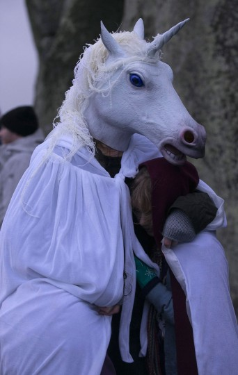 A woman wearing a unicorn mask shelters a girl as druids, pagans and revellers gather, hoping to see the sun rise as they take part in a winter solstice ceremony at Stonehenge on December 21, 2013 in Wiltshire, England. Despite the rain and wind, a large crowd gathered at the famous historic stone circle to celebrate the sunrise closest to the Winter Solstice, the shortest day of the year - an event claimed to be more important in the pagan calendar than the summer solstice, because it marks the 're-birth' of the Sun for the New Year.