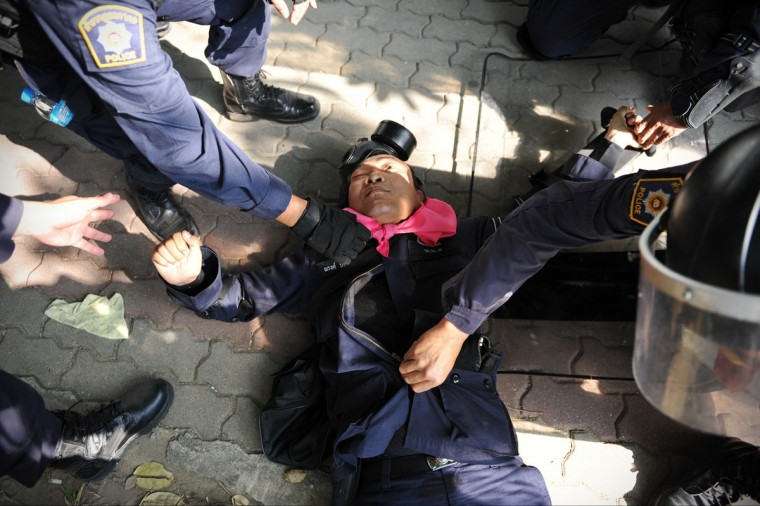 A policeman lies injured from a gunshot wound to the chest after police come under fire at a sports stadium where the Thai Election Commission is registering candidates for Thailand's upcoming poll on December 26, 2013 in Bangkok, Thailand. The policeman later died of his injuries. Several thousand anti-government protesters clashed with police guarding the election registration venue. Police used tear gas, rubber bullets and waters canons, while gunfire was heard on several occasions from both sides of the police line. Protesters demand that the election be called off and an appointed government takes power until political reforms have taken place. (Rufus Cox/Getty Images)