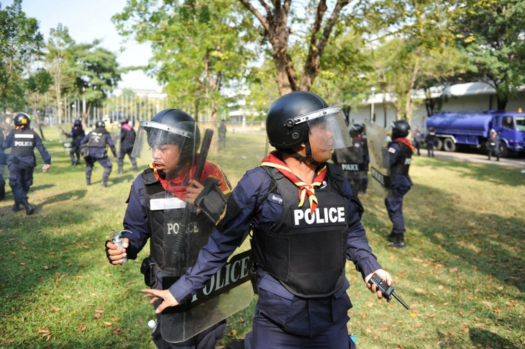 Policemen react after coming under gunshot fire at a sports stadium where the Thai Election Commission is registering candidates for Thailand's upcoming poll on December 26, 2013 in Bangkok, Thailand. One policeman died of gunshot injuries. Several thousand anti-government protesters clashed with police guarding the election registration venue. Police used tear gas, rubber bullets and waters canons, while gunfire was heard on several occasions from both sides of the police line. Protesters demand that the election be called off and an appointed government takes power until political reforms have taken place. (Rufus Cox/Getty Images)