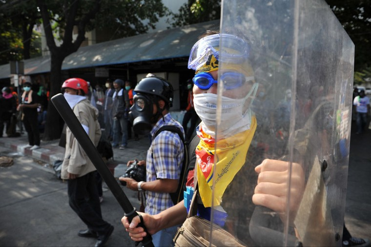 An anti-government protesters armed with a batton and riot shield takes part in violent protest at a sports stadium where the Thai Election Commission is registering candidates for Thailand's upcoming poll on December 26, 2013 in Bangkok, Thailand. Several thousand anti-government protesters fought with police guarding the election registration venue. Police used tear gas, rubber bullets and waters canons, while gunfire was heard on several occasions from both sides of the police line. One policeman died of a gunshot wound, while nearly one hundred people were injured during the clashes, including protesters, police and media. Protesters demand that the election be called off and an appointed government takes power until political reforms have taken place. (Rufus Cox/Getty Images)
