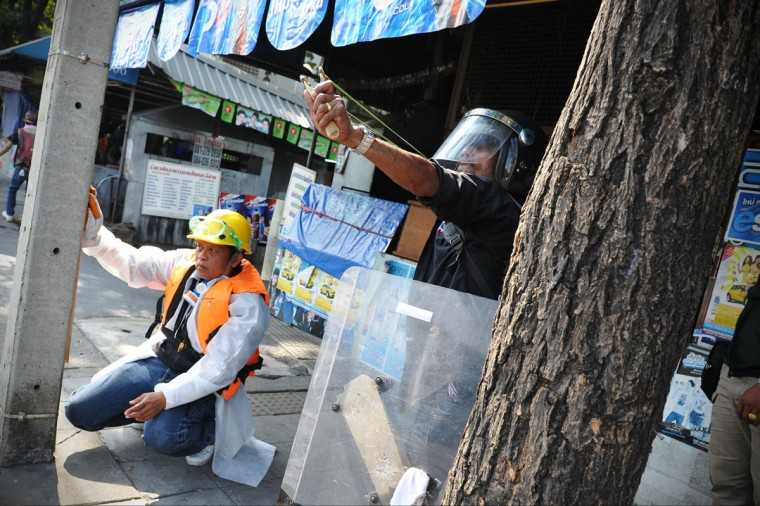An anti-government protester readies a slingshot during clashes with police at a sports stadium where the Thai Election Commission is registering candidates for Thailand's upcoming poll on December 26, 2013 in Bangkok, Thailand. Several thousand anti-government protesters fought with police guarding the election registration venue. Police used tear gas, rubber bullets and waters canons, while gunfire was heard on several occasions from both sides of the police line. One policeman died of a gunshot wound, while nearly one hundred people were injured during the clashes, including protesters, police and media. Protesters demand that the election be called off and an appointed government takes power until political reforms have taken place. (Rufus Cox/Getty Images)