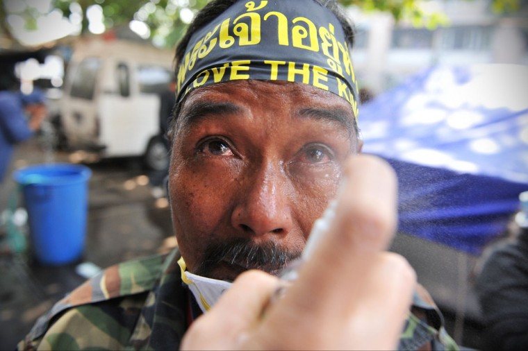 An anti-government protesters overcome by tear gas has his eyes rinsed with saline during a violent protest at a sports stadium where the Thai Election Commission is registering candidates for Thailand's upcoming poll on December 26, 2013 in Bangkok, Thailand. Several thousand anti-government protesters fought with police guarding the election registration venue. Police used tear gas, rubber bullets and waters canons, while gunfire was heard on several occasions from both sides of the police line. One policeman died of a gunshot wound, while nearly one hundred people were injured during the clashes, including protesters, police and media. Protesters demand that the election be called off and an appointed government takes power until political reforms have taken place. (Rufus Cox/Getty Images)