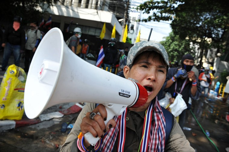 An anti-government protester shouts slogans into a loud hailer while taking part in a violent protest at a sports stadium where the Thai Election Commission is registering candidates for Thailand's upcoming poll on December 26, 2013 in Bangkok, Thailand. Several thousand anti-government protesters fought with police guarding the election registration venue. Police used tear gas, rubber bullets and waters canons, while gunfire was heard on several occasions from both sides of the police line. One policeman died of a gunshot wound, and nearly one hundred people were injured during the clashes, including protesters, police and media. Protesters demand that the election be called off and an appointed government takes power until political reforms have taken place. (Rufus Cox/Getty Images)