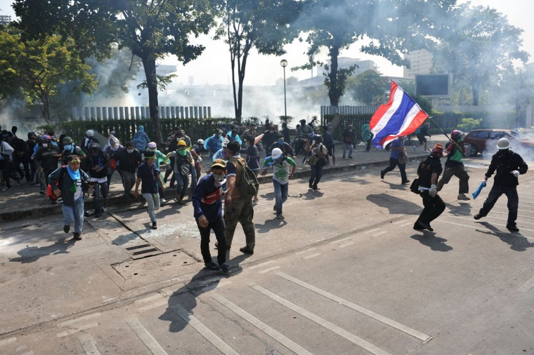 Anti-government protesters retreat after police fire tear gas and rubber bullets during a violent protest at a sports stadium where the Thai Election Commission is registering candidates for Thailand's upcoming poll on December 26, 2013 in Bangkok, Thailand. Several thousand anti-government protesters fought with police guarding the election registration venue. Police used tear gas, rubber bullets and waters canons, while gunfire was heard on several occasions from both sides of the police line. One policeman died of a gunshot wound and nearly one hundred people were injured during the clashes, including protesters, police and media. Protesters demand that the election be called off and an appointed government takes power until political reforms have taken place. (Rufus Cox/Getty Images)