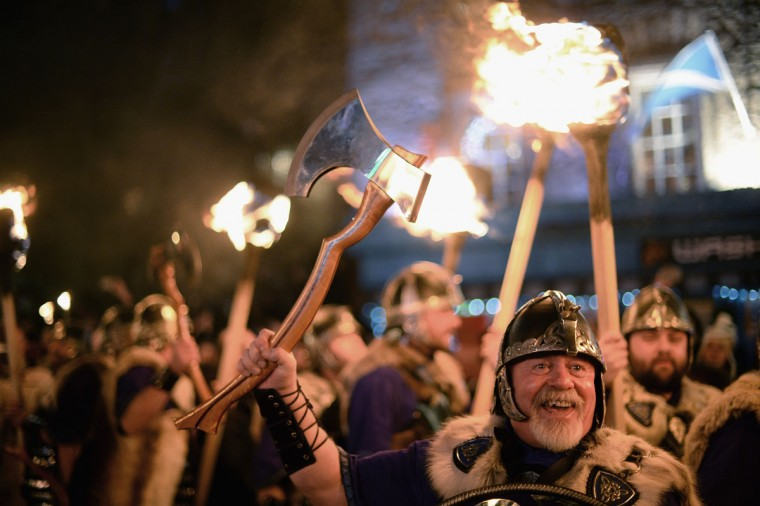 A man dressed as a Viking takes part in the torchlight procession as it makes its way through Edinburgh for the start of the Hogmanay celebrations on December 30, 2013 in Edinburgh, Scotland. Around 80,000 people are expected in the city for the traditional New Year celebrations, which run over three days. Tickets have been bought for the event by people from over sixty different countries. (Jeff J Mitchell/Getty Images)