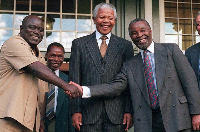 Zaire's rebel leader Laurent-Desire Kabila (L) shakes hands with South African Deputy President Thabo Mbeki (R), while President Nelson Mandela looks on, 16 April at Tuynhuis in Cape Town, prior to discussions on the Zaire conflict. (Anna Zieminski/AFP/Getty Images)