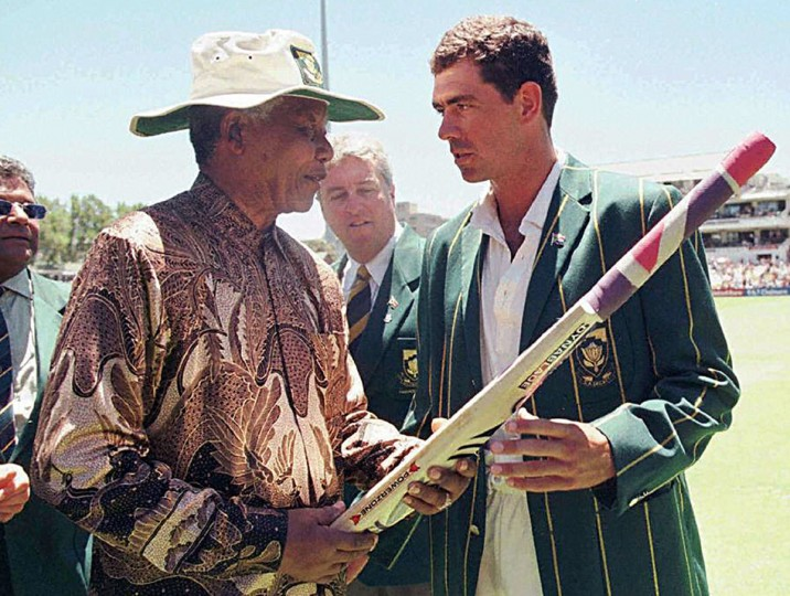 South African President Nelson Mandela receives a cricket bat from the South African Cricket captain, Hansie Cronje, during the lunch break on the third day of the Second Test between South Africa and India at Newlands on January 4, 1997. (Adil Bradlow/AFP/Getty Image)