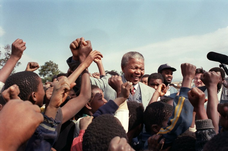 ANC president Nelson Mandela is surrounded by young supporters after addressing residents at Phola Park, a squatter settlement east of Johannesburg, 31 May 1992. (Walter Dhladh/AFP/Getty Images)