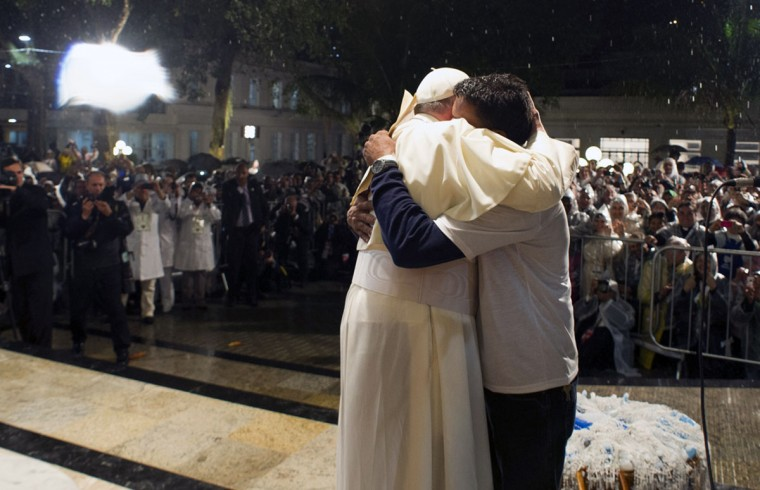 """Pope Francis (C) hugs a drug addict during his visit to the St. Francis Hospital in Rio de Janeiro, Brazil, on July 24, 2013. Pope Francis warned Catholics against """"ephemeral idols"""" like money at his first public mass in his native Latin America as huge crowds lined the streets to cheer him. The first Latin American and Jesuit pontiff visited Aparecida to lead his first big mass since arriving in the country for a week-long visit of which highlight is the huge five-day Catholic gathering World Youth Day. (Observatore Romano/AFP/Getty Images)"""