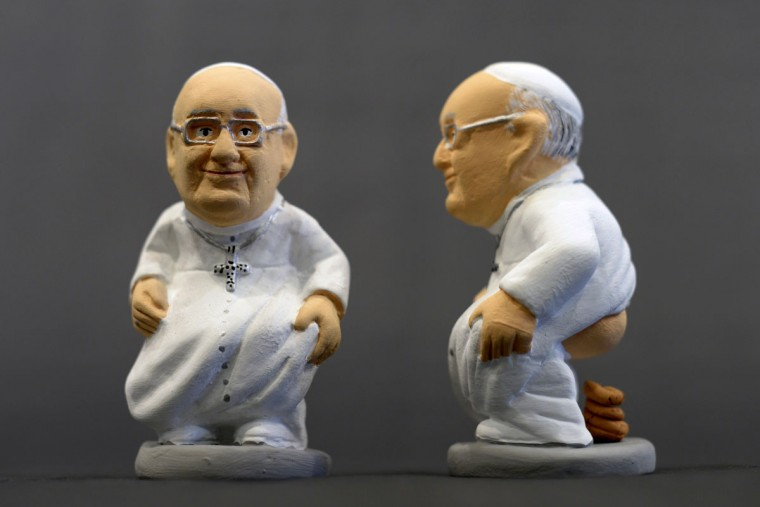 """Ceramic figurines of Pope Francis called """"Caganers"""" are pictured during their presentation in Torroella de Montgri, near Gerona on November 15, 2013. Statuettes of well-known people defecating are a strong Christmas tradition in Catalonia, dating back to the 18th century as Catalonians hide caganers in Christmas Nativity scenes and invite friends to find them. The figures symbolize fertilization, hope and prosperity for the coming year. (Lluis Genelluis/AFP/Getty Images)"""