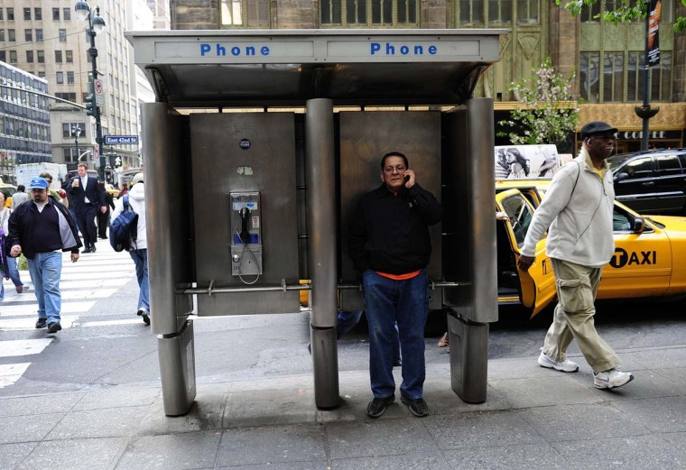 "A man uses an empty public pay phone booth to shield himself from street noise while making a call with his mobile phone, in New York, in this April 9, 2012 file photo. The plain old telephone network is rapidly being overtaken in the United States by new technology, putting regulators in a quandary over how to manage the shift. The Federal Communications Commission said it will discuss proposals at its December 12 meeting, with the aim of drafting order in January to formalize the ""IP transition,"" or switching communications systems to Internet protocol. It's not clear how or when the FCC would phase out the remnants of the telephone network, and what it would mean for roughly 100 million Americans who still rely on the dated by still-functional system of copper wires and switching stations. FCC Chairman Tom Wheeler, confirmed just last month to head the regulatory agency, said the technological advance ""is a good thing,"" adding that ""history has shown that new networks catalyze innovation, investment, ideas, and ingenuity."" AFP/Getty Images file photo by EMMANUEL DUNAND"