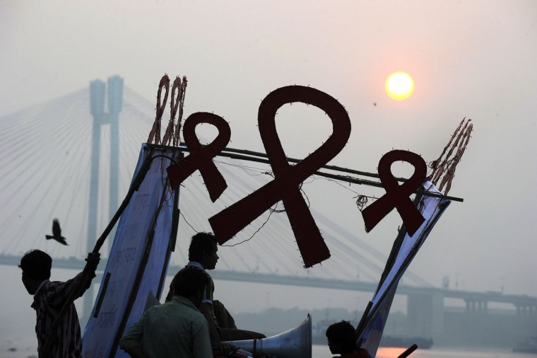 Indian NGO workers arrange banners and red ribbon cutouts on a boat along the holy river Ganges to highlight AIDS awareness on the eve of World AIDS Day in Kolkata, India on November 30, 2013. World AIDS Day is celebrated on December 1 every year to raise awareness about HIV/AIDS and to demonstrate international solidarity in the face of the pandemic. (Dibyangshu Sarkar/AFP/Getty Images)
