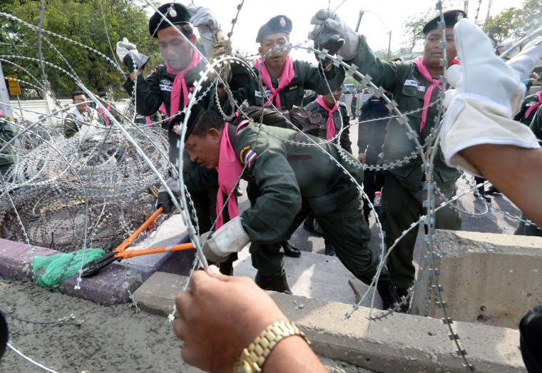 Thai policemen cut a barbed wire fence to open barricades at the Metropolitan police headquarters in Bangkok on December 3, 2013. Hundreds of Thai opposition protesters entered the government headquarters unopposed on December 3, after police said they would offer no resistance to the demonstrators who have vowed to topple Prime Minister Yingluck Shinawatra. (Indranil Mukherjee/AFP/Getty Images)