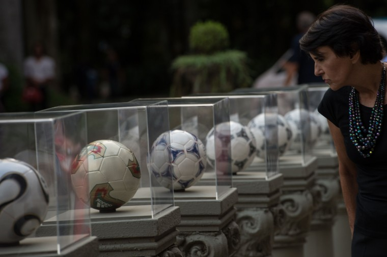 A woman looks at official balls of the FIFA World Cup, dating back to 1970, before the launch of Brazuca, the official ball for the Brazil 2014 FIFA World Cup in Rio de Janeiro, Brazil, (YOSHI CHIBA/AFP/Getty Images)