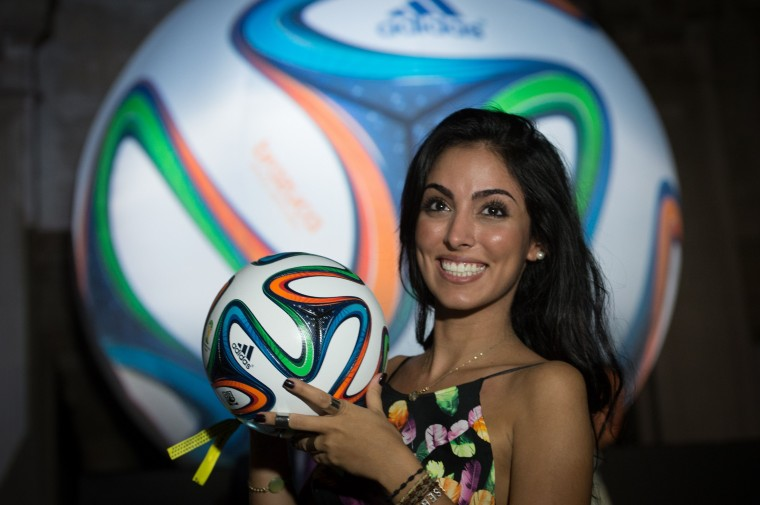 A woman poses with Brazuca, the official ball for the Brazil 2014 FIFA World Cup, during its launching in Rio de Janeiro, Brazil. (YOSHI CHIBA/AFP/Getty Images)