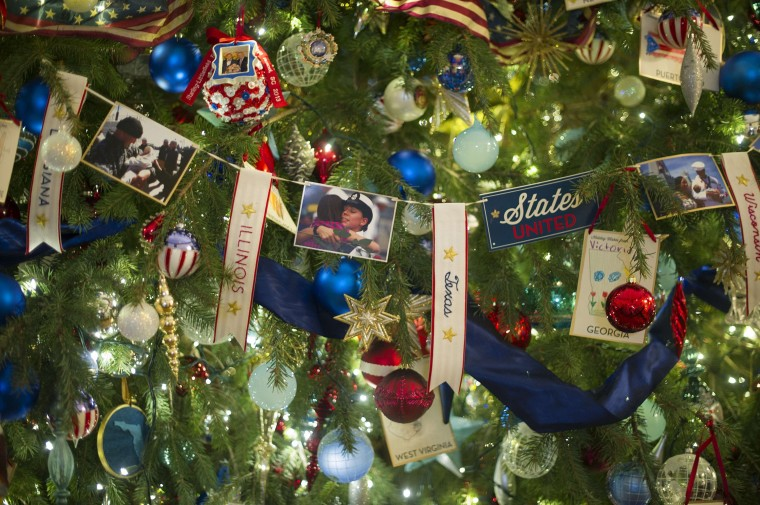 Decorations honoring military families hang upon the official White House Christmas tree in the Blue Room at the White House in Washington, DC, December 4, 2013 during the White House Christmas decorations viewing. (Jim Watson/AFP/Getty Images)