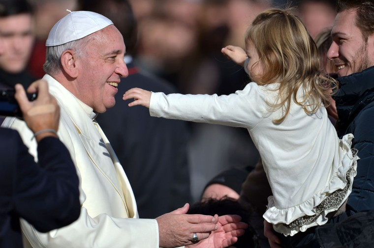 Pope Francis is about to hug a young girl during his general audience in St Peter's square at the Vatican. (FILIPPO MONTEFORTE / AFP/Getty Images)