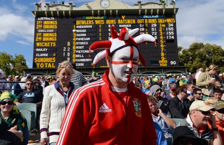 An England fan walks in front of the famous Adelaide Oval scoreboard on the first day of the second Ashes Test cricket match between Australia and England in Adelaide. (WILLIAM WEST / AFP/Getty Images)