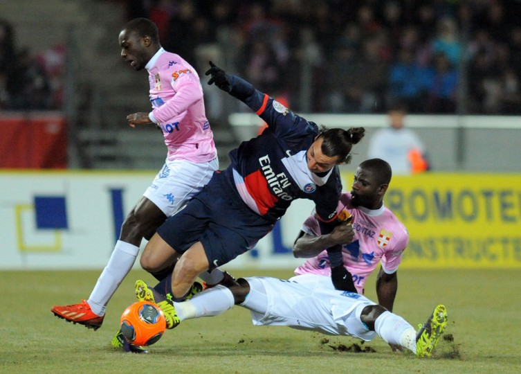 Paris Saint-Germain's Swedish forward Zlatan Ibrahimovic (center) challenges Evian TG's Senegalese forward Modou Sougou (right) during the French L1 football match between Evian Thonon-Gaillard and Paris Saint-Germain at the Parc des Sports stadium in Annecy, eastern France. (JEAN-PIERRE CLATOT / AFP/Getty Images)