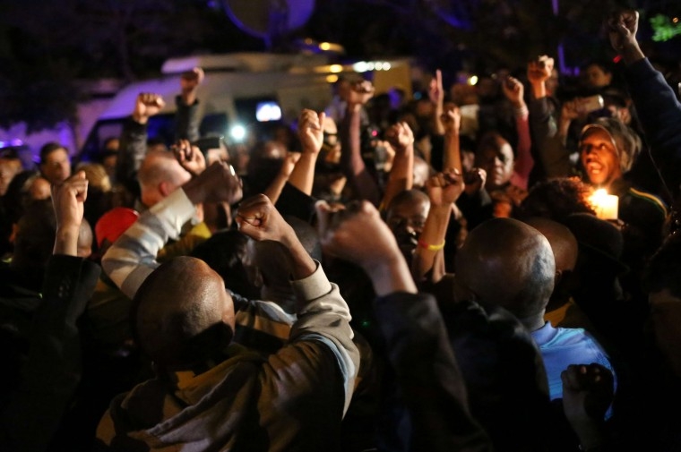 South Africans react as they pay tribute to former South African president Nelson Mandela following his death in Johannesburg on December 5, 2013. Mandela, the revered icon of the anti-apartheid struggle in South Africa and one of the towering political figures of the 20th century, has died aged 95. Mandela, who was elected South Africa's first black president after spending nearly three decades in prison, had been receiving treatment for a lung infection at his Johannesburg home since September, after three months in hospital in a critical state. (Alexander Joe/AFP/Getty Images)