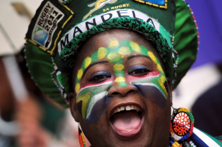 A woman celebrates in the tribune before the memorial service for Nelson Mandela on December 10, 2013 at Soccer City Stadium in Johannesburg, South Africa. Mandela, the revered icon of the anti-apartheid struggle in South Africa and one of the towering political figures of the 20th century, died in Johannesburg on December 5 at age 95. Mandela, who was elected South Africa's first black president after spending nearly three decades in prison, had been receiving treatment for a lung infection at his Johannesburg home since September, after three months in hospital in a critical state. (Alexander Joe/AFP/Getty Images)