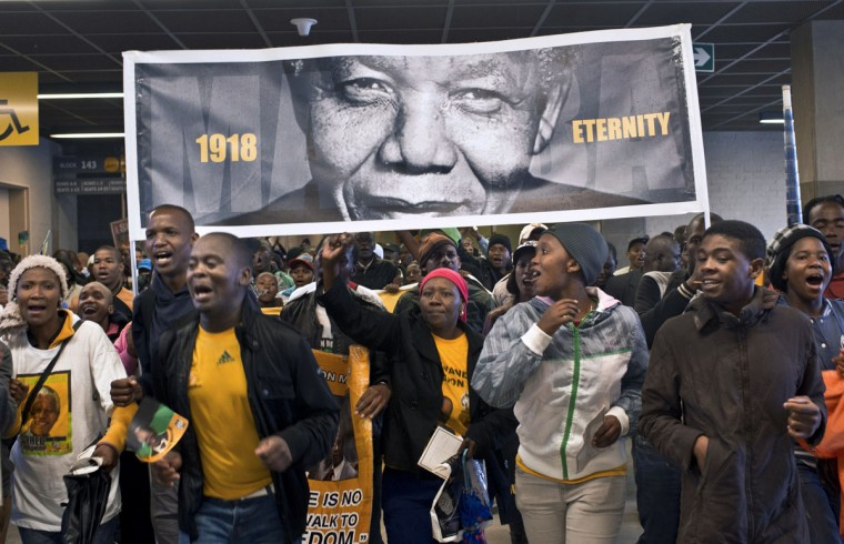People holding a giant portrait of Nelson Mandela arrive moments before the memorial service on December 10, 2013 at Soccer City Stadium in Johannesburg. Mandela, the revered icon of the anti-apartheid struggle in South Africa and one of the towering political figures of the 20th century, died in Johannesburg on December 5 at age 95. (Pedro Ugarte/AFP/Getty Images)