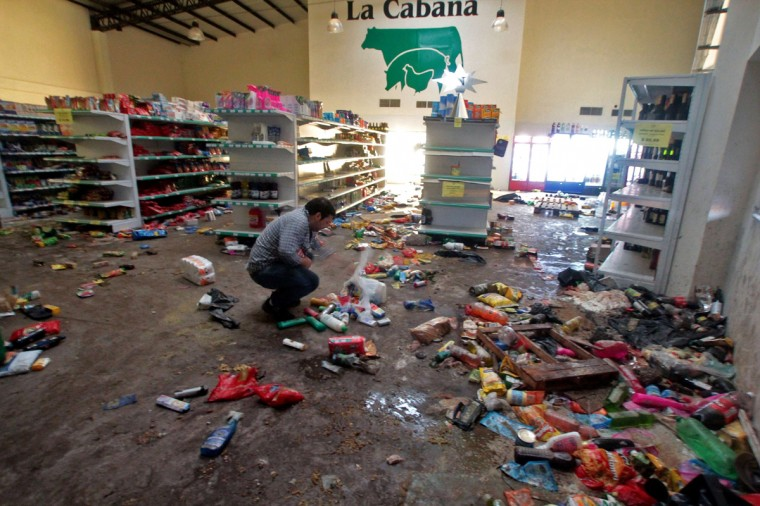 A man remains at a looted store in the outskirts of Tucuman, northern Argentina on December 9, 2013. Seven people died overnight in looting in northern Argentina sparked by a police strike, authorities said Tuesday. The total number of fatalities now stands at nine, they said, with hundreds of others injured and dozens arrested. Riots and looting first erupted in the city of Cordoba a week ago after police demanding higher wages refused to go on patrol there. (Walter Monteros/AFP/Getty Images)