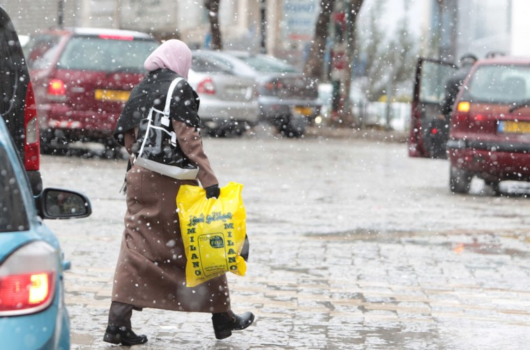 A Palestinian woman walks through Ramallah's main square during snowfall in the West Bank on December 12, 2013. (MUSA AL-SHAERABBAS MOMANI / AFP/Getty Images)