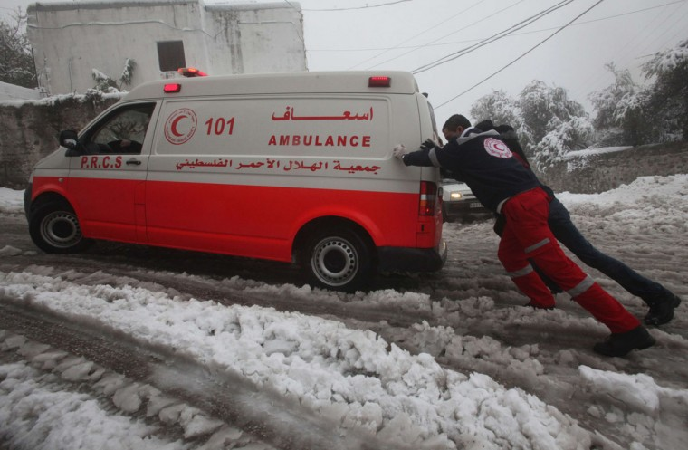A member of the Palestinian ambulance team is helped by a Palestinian man to push an ambulance in the snow in the West Bank town of Hebron on December 12, 2013. (HAZEM BADER / AFP/Getty Images)