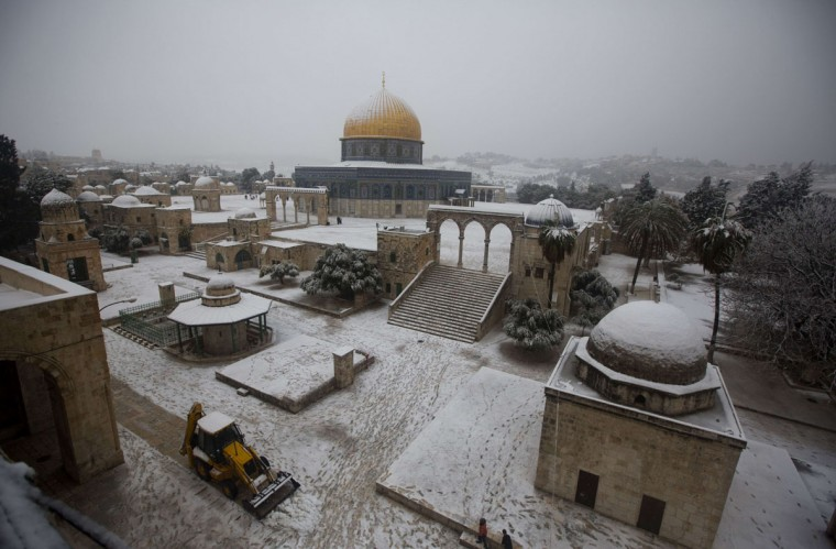 A bulldozer shifts snow near the Dome of the Rock at the Al-Aqsa mosque compound in the old city of Jerusalem on December 12, 2013. (AHMAD GHARABLI / AFP/Getty Images)
