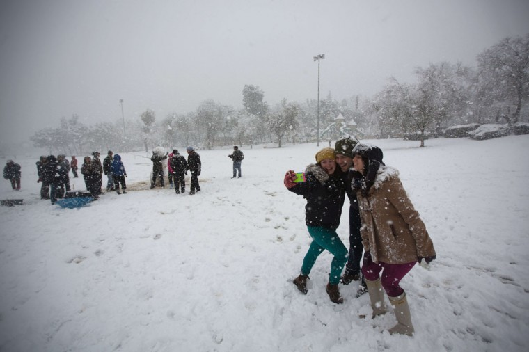 Israelis take a selfie in Jerusalem as snow falls on December 12, 2013. (MENAHEM KAHANA / AFP/Getty Images)
