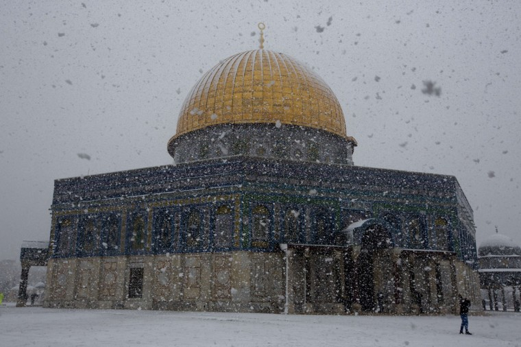 Snow falls over the Dome of the Rock at the Al-Aqsa mosques compound in the old city of Jerusalem on December 12, 2013. (AHMAD GHARABLI / AFP/Getty Images)
