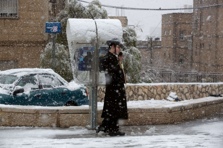 An Ultra-orthodox Jewish man uses a public phone as snow falls Jerusalem on December 12, 2013. (MENAHEM KAHANA / AFP/Getty Images)
