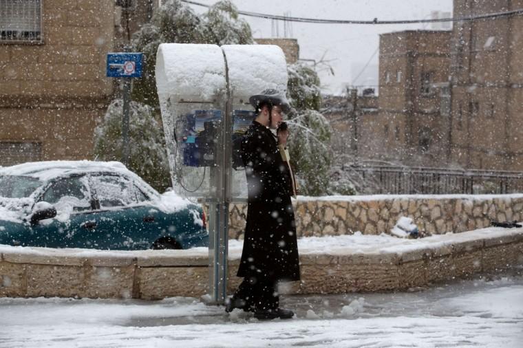 An Ultra-orthodox Jewish man uses a public phone as snow falls Jerusalem on December 12, 2013. (MENAHEM KAHANA / AFP/Getty Images)