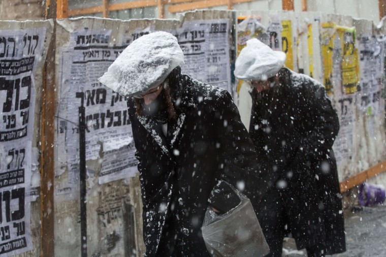 Ultra-orthodox Jewish men protect their heads with plastic bags during snowfall in Jerusalem on December 12, 2013. (MENAHEM KAHANA / AFP/Getty Images)