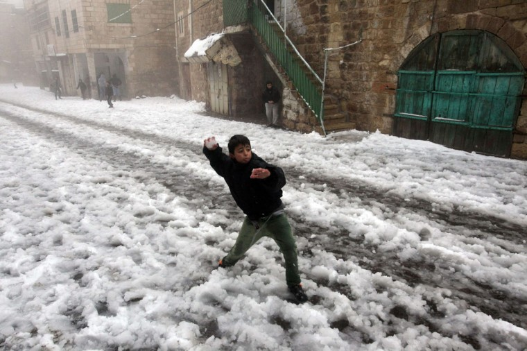A boy throws a snowball near Ibrahimi Mosque or the Tomb of the Patriarch, a religious site to both Muslims and Jews, in the West Bank town of Hebron as snow falls on December 12, 2013. (HAZEM BADER / AFP/Getty Images)