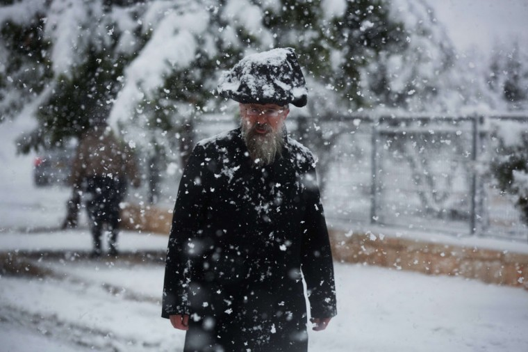 An ultra-orthodox Jewish man walks during a snowstorm in Jerusalem on December 12, 2013. (MENAHEM KAHANA / AFP/Getty Images)