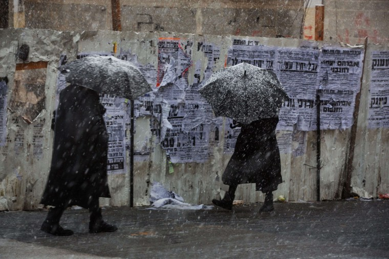 Ultra-orthodox Jewish men walk during a snowstorm in Jerusalem on December 12, 2013. (MENAHEM KAHANA / AFP/Getty Images)