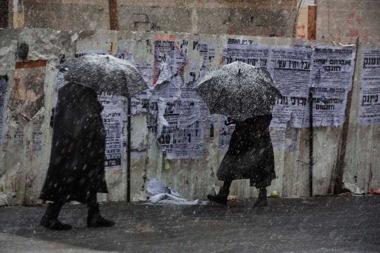 Ultra-orthodox Jewish men walk during a snowstorm in Jerusalem on December 12, 2013. (MENAHEM KAHANA / AFP/Getty Images)
