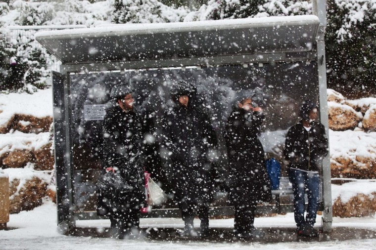 Ultra-orthodox Jewish men wait at a bus station during a snowstorm in Jerusalem on December 12, 2013. (MENAHEM KAHANA / AFP/Getty Images)