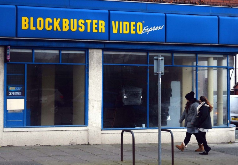 People walk past a closed branch of Blockbuster in Wallasey, northwest England, on December 12, 2013. Blockbuster is to shut down all its remaining stores within days after administrators were unable to find a buyer for the rental and DVD chain. (PAUL ELLIS/AFP/Getty Images)