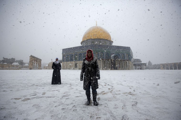 Two Palestinian women stand in front of the Dome of the Rock at the Al-Aqsa mosques compound during snow fall on the holy city of Jerusalem on December 12, 2013 (AHMAD GHARABLI / AFP/Getty Images)