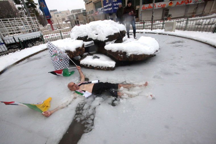 A Palestinian man poses for pictures with his national and the Fatah party flags as he lies in a half-frozen fountain in the West Bank town of Hebron after snow fall on December 12, 2013. (HAZEM BADER / AFP/Getty Images)