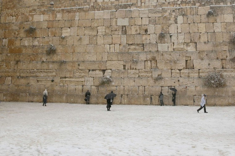 Jewish men pray by the Western Wall as snow falls in the Jerusalem's old city on December 12, 2013. (GALI TIBBON / AFP/Getty Images)
