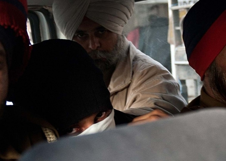 In this photograph taken on December 12, 2013, Indian national Puneet Puneet (C) hides his face while being transported in a police vehicle from the Patiala House courts in New Delhi. An Indian man who fled Australia after killing a teenager while drink driving and speeding in Melbourne was on December 13, 2013 sent to prison as a court set his extradition hearing for this week. (MANAN VATSYAYANA/AFP/Getty Images file photo)