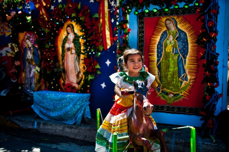 A girl poses for a picture in a makeshift photo studio outside the Basilica de Guadalupe church in San Salvador, El Salvador on December 12, 2013 during the celebration of the Virgin of Guadalupe. (JOSE CABEZAS / AFP/Getty Images)