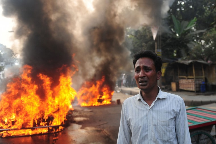 A Bangladeshi vehicle owner reacts near a burning car set on fire by demonstrating Jamaat-e-Islami supporters following the execution of Abdul Quader Molla, a top Islamist leader convicted of war crimes, in Dhaka on December 13, 2013. (MUNIR UZ ZAMAN / AFP/Getty Images)