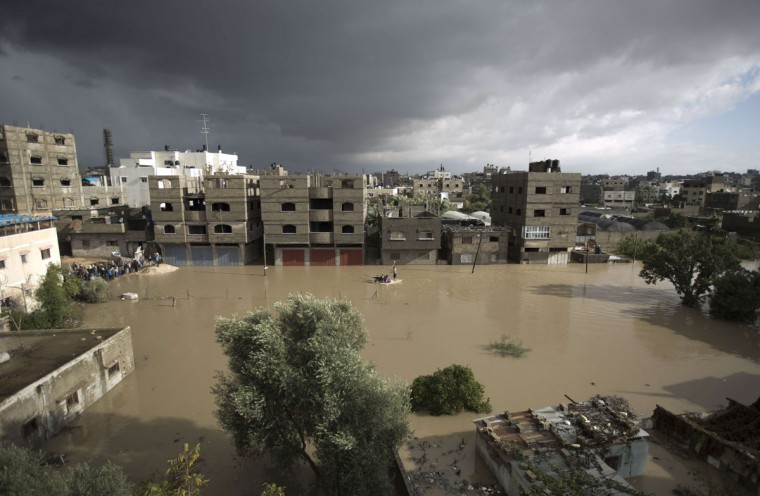 Members of the Palestinian civil defense ride a boat as they evacuate a family in Gaza City following heavy rainfall on December 13, 2013. (MOHAMMED ABED / AFP/Getty Images)